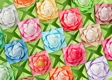 Origami roses. Colourful paper roses on a green background Stock Image
