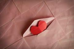 Origami rouge de papier de coeur à l'arrière-plan rose d'enveloppe Photo stock