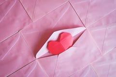 Origami rouge de papier de coeur à l'arrière-plan rose d'enveloppe Photos stock