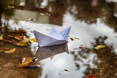 Origami Ship, Paper Boat sails in a puddle formed after rain. Winter in Israel. Origami Ship, Paper Boat sails in a puddle formed after rain. Winter in Israel royalty free stock photo