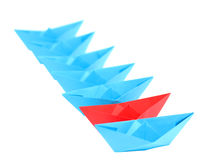 Origami.Ships standing in a row. Origami. Ranked blue ships. One boat red. Focus on the red boat Stock Photos
