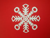 Origami snowflake. Made from white paper and isolated on red Stock Images