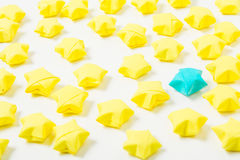 Origami stars. Many yellow and one blue origami stars on the white background Royalty Free Stock Photos