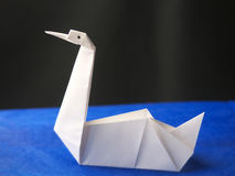 Origami swan on blue background Royalty Free Stock Image