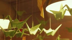 Origami swans hanging under the lights as an ornamental decoration in interior. 1920x1080 stock footage