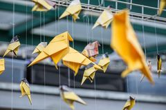 Origami yellow orange paper cranes birds hanging over industrial architectural blurred background.  Royalty Free Stock Photo