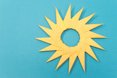 Origami yellow paper sun isolated on blue Stock Photography
