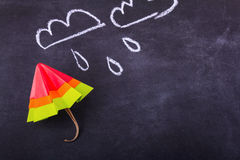 Origami yellow red blue cartoon protection umbrella on a white background. Origami cartoon protection umbrella on a blackboard background with drops and clouds Stock Images