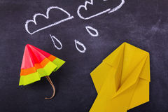 Origami yellow red blue cartoon protection umbrella on a white background. Origami cartoon protection umbrella and raincoat on a blackboard background with drops Stock Photo