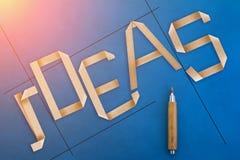 Origamiart-Ideenwort auf blauem ledernem Hintergrund Lizenzfreie Stockfotografie