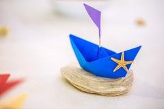 Origamiboot des blauen Papiers mit Starfish und Muschel, Hochzeitstafeldekoration Lizenzfreies Stockfoto