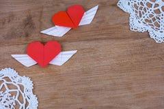 Origamiherzen mit Flügeln auf einem hölzernen Hintergrund mit Spitze Stockfotografie