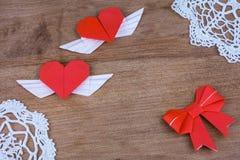 Origamiherzen mit Flügeln auf einem hölzernen Hintergrund mit Spitze Zwei Innere Stockfotografie