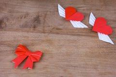 Origamiherzen mit Flügeln auf einem hölzernen Hintergrund Zwei Innere Stockbild