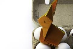 Origamikonijn van oranje document Paashaas en witte kippeneieren in een vakje, exemplaarruimte royalty-vrije stock afbeelding