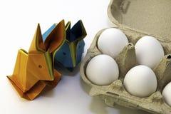 Origamikonijnen van gekleurd document Pasen-hazen en witte kippeneieren in een doos stock foto