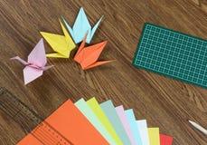 Origamikräne, buntes Papier, Schneidematte und Bleistift auf Holztisch Stockbilder