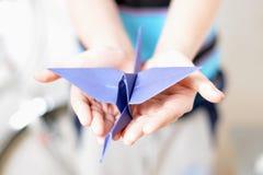 Origamikran in den Händen der Kinder Lizenzfreie Stockfotos
