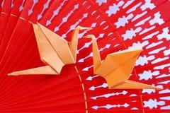 Origamikranen van document op rode ventilator - Voorraadfoto Stock Afbeeldingen