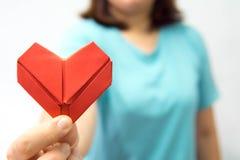 Origamin för en hjärta för asiatkvinna som skyler över brister den hållande är främst av hennes kvinna för bröstkorg som A ger rö fotografering för bildbyråer