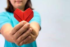 Origamin för en hjärta för asiatkvinna som skyler över brister den hållande är främst av hennes kvinna för bröstkorg som A ger rö royaltyfria bilder