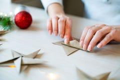Origamin för kvinnahandvikning skyler över brister stjärnan för julgarnering royaltyfri bild