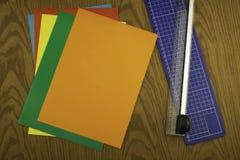 Origamin för pappers- skärare och färgskyler över brister på en trätabell arkivfoto