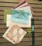 Origamin skyler över brister, tillverkar material på den spjälade Wood tabellen Arkivfoton