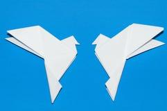 Origamitauben auf einem blauen Hintergrund Stockfotos