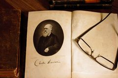 The origin of species by Charles Darwin opened on first page with glasses on the second page. Charles Darwin`s `The origin of species` German translation, 4th stock photo