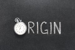 Origin word watch. Origin word handwritten on chalkboard with vintage precise stopwatch used instead of O stock image