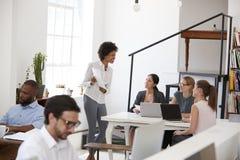 Originais de apresentação da mulher aos colegas em uma mesa no escritório fotos de stock