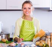 Originais de enchimento da dona de casa na cozinha Fotografia de Stock