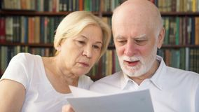 Originais financeiros do investimento superior da leitura dos pares Família de pensionista aposentados com relatório do imposto vídeos de arquivo