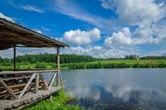 Arbor for rest of wooden logs on the shore of a picturesque lake or river with green coasts against the background of beautiful na. The original arbor for rest stock photo