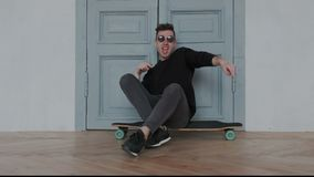 Original and authentic young guy in a cool sunglasses dancing, singing and have fun while sitting on the longboard or stock video