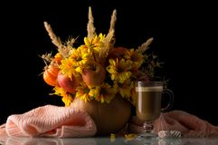 Original autumn composition in pumpkin, nearby Cup of cappuccino and warm scarf isolated on black royalty free stock photo