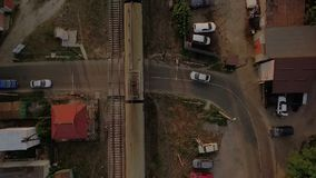 Aerial shot of a moving train crossing the asphalt road with cars. An original bird`s eye view of a moving train crossing the asphalt road with cars. The parking stock video