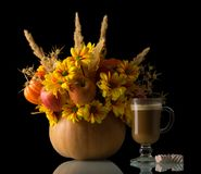 Original bouquet in pumpkin, cup of cappuccino and marshmallows, isolated on black Stock Photo