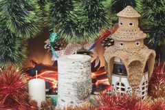 Original ceramic house painted with glaze, colored tinsel, homemade birch candlestick, candle with cones of garlands, and pine con royalty free stock photos