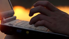 Male Fingers Type on a pc Keyboard Outdoor on a River Bank at Night. An Original Close-Up of Male Fingers Which Type on a Gray pc Keyboard Outdoor on a River stock video