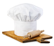 Original cooks cap with wooden rolling-pin on a wooden cutting board. Royalty Free Stock Image