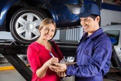 Original de assinatura do cliente com mecânico In Garage imagens de stock royalty free