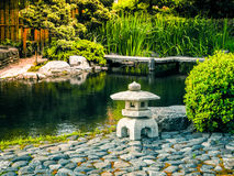 The original design of the landscape in the Japanese style. Stone lantern placed near the pond in the Japanese garden. Royalty Free Stock Photography