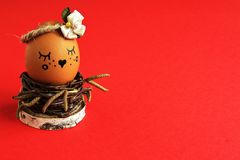 Charming coquettish light brown egg with satin flower in pastel ton in homemade wicker of birch twigs in nest on red background. Original egg with decorative royalty free stock photo