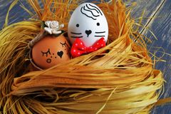 Charming flirty light brown egg with satin flower in bed tones and white egg with red tie butterfly in bast nest on dark old. Original egg with decorative flower royalty free stock photo