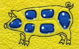 Embroidered pig on a yellow background stock images