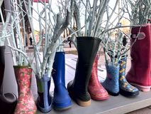 Original exposed colored rubber boots near the entrance to the store stock photo