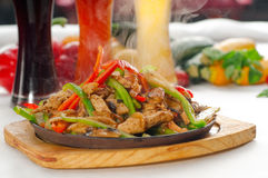 Original fajita sizzling hot  on iron plate. Original fajita sizzling smoking hot served on iron plate ,with selection of beer and fresh vegetables on background Stock Images