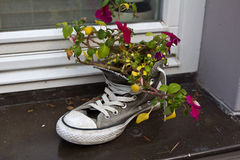 The original flower pot. Shoes instead of a flower pot on the windowsill stock photos
